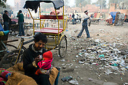 A homeless rickshaw wallah gives his baby child a drink of tea at dawn in Urdu Park a notorious area for the destitute and drug addicts near the Jama Masjid, Delhi, India.