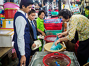 """14 FEBRUARY 2019 - SIHANOUKVILLE, CAMBODIA:  Cambodians who work in a Chinese casino in Sihanoukville buy shrimp in a market stall after their shift. There are about 80 Chinese casinos and resort hotels open in Sihanoukville and dozens more under construction. The casinos are changing the city, once a sleepy port on Southeast Asia's """"backpacker trail"""" into a booming city. The change is coming with a cost though. Many Cambodian residents of Sihanoukville  have lost their homes to make way for the casinos and the jobs are going to Chinese workers, brought in to build casinos and work in the casinos.      PHOTO BY JACK KURTZ"""