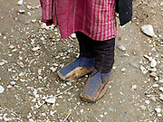 A Brokpa woman wearing traditional yak skin shoes in Merak, Eastern Bhutan. The Brokpa, the semi-nomads of the villages of Merak and Sakteng are said to have migrated to Bhutan a few centuries ago from the Tshona region of Southern Tibet. Thriving on rearing yaks and sheep, the Brokpas have maintained many of their unique traditions and customs. Given the geographic isolation of many of Bhutan's villages, there are 16 different dialects and 14 regional groups in the country. Many tribes have kept alive their distinct cultural identities through their dress, language and traditions over the years.