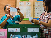 07 AUGUST 2016 - BANGKOK, THAILAND:  An elections worker holds up a marked ballot in a polling place in Bangkok Sunday. Thais voted Sunday in the referendum to approve a new charter (constitution) for Thailand. The new charter was written by a government appointed panel after the military coup that deposed the elected civilian government in May, 2014. The charter referendum is the first country wide election since the coup. Elections workers counted the votes in the polling places after the polls closed at 16.00.      PHOTO BY JACK KURTZ