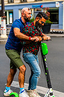 Gay men riding an electric scooter together,  near Boulevard Montparnasse, Paris, France.