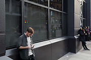 A young man uses his phone while vaping outside offices on a Farringdon Road, on 20th November 2019, in the City of London, England.