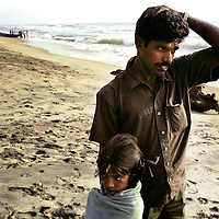 Viswanathan, and his seven year-old daughter Vijyashsree, looks out across the sea close to the point where his wife and son lost their lives in the Asian Tsunami. Since then Viswanathan has remarried and now has two children by his second wife.<br /> <br /> Photo: Tom Pietrasik<br /> Tamil Nadu, India. 2005