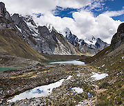 Siula Lake (14,000 ft or 4290 m, greenish) and stream ponds lie at the feet of massive peaks such as Nevado Jirishanca (Icy Beak of the Hummingbird, 6126 m or 20,098 feet) in the Cordillera Huayhuash, Andes Mountains, Peru, South America. Day 3 of 9 days trekking around the Cordillera Huayhuash. This panorama was stitched from 3 overlapping photos.