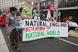 Stop HS2 activists hold a banner criticising Natural England during the Extinction Rebellion March for Nature on the final day of the two-week Impossible Rebellion on 4th September 2021 in London, United Kingdom. Extinction Rebellion are calling on the UK government to cease all new fossil fuel investment with immediate effect.