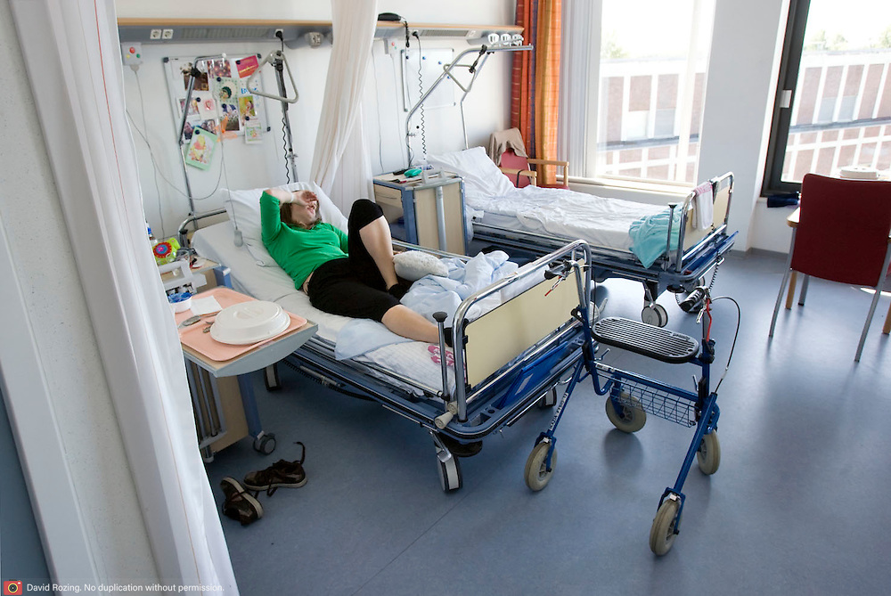 Nederland Rotterdam  31-08-2009 20090831 Foto: David Rozing .VOOR GEBRUIK EERST OVERLEG Serie over zorgsector, Ikazia Ziekenhuis Rotterdam. Afdeling neurologie. Jonge vrouw op zaal ligt in ziekenhuisbed, zij is moe en rust uit nadat zij revalidatie oefeningen heeft gedaan. Aan het voeteneind van het bed staat haar rollator, ze is deels verlamd.  Woman patient in hospital bed, resting after doing revalidation excercises. .Foto: David Rozing ..Holland, The Netherlands, dutch, Pays Bas, Europe, op zaal liggen, revalidatie, revalideren, revalidation,mobiliteit, niet mobiel zijn, gedeeltelijk verlamd zijn, verlamming, niet goed kunnen lopen, mobiel, hulpmiddel, loopwagentje, loopkarretje, slechte motoriek, overzicht, general view, rollator,ziektekosten,zorgverlening, vermoeid, moe zijn, rust, rusten, uitrusten, het zwaar hebben,,paralysis, paralysed, verlamming, jong, jeugdig, jeugdige, meid,