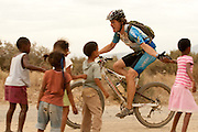A rider joins in the local childrens excitement during stage 3 of the 2011 Absa Cape Epic Mountain Bike stage race held from Saronsberg Wine Estate in Tulbagh to Worcester Gymnasium in Worcester, South Africa on the 30 March 2011..Photo by Greg Beadle/Cape Epic/SPORTZPICS
