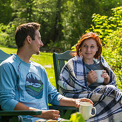 A young couple enjoy their morning coffee at the Appalachian Mountain Club's Gorman Chairback Lodge. Near Greenville, Maine.