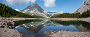 Mount Worthington (2915 m or 9564 ft) reflects in Three Isle Lake (2180 m) in Peter Lougheed Provincial Park, Kananaskis Country, Alberta, Canada. This image was stitched from multiple overlapping photos.