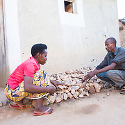 CAPTION: Stanislas' home is his pride and joy, and he lovingly keeps it in a very good condition. Here, he and Clementine are placing rocks around the walls to help protect against water, as this is one of Rwanda's rainy seasons. Stanislas' living conditions have changed significantly, however. Initially, upon his return from prison and then public work, his house was in a state of severe disrepair, with walls riddled with holes. Life as a whole was very difficult then, and it was a struggle to watch his children come close to starvation while not having access to safe shelter. The FRW 15,000 (€ 20) that was given every month for 18 months helped him to stabilise the household, take care of his family's needs, send his children to school, rent land for small-scale agriculture and buy small animals. LOCATION: Rushikiri Village, Kimuna Cell, Rusatira Sector, Huye District, South Province, Rwanda. INDIVIDUAL(S) PHOTOGRAPHED: Clementine Nibagwire (left) and Stanislas Iriboneye (right).