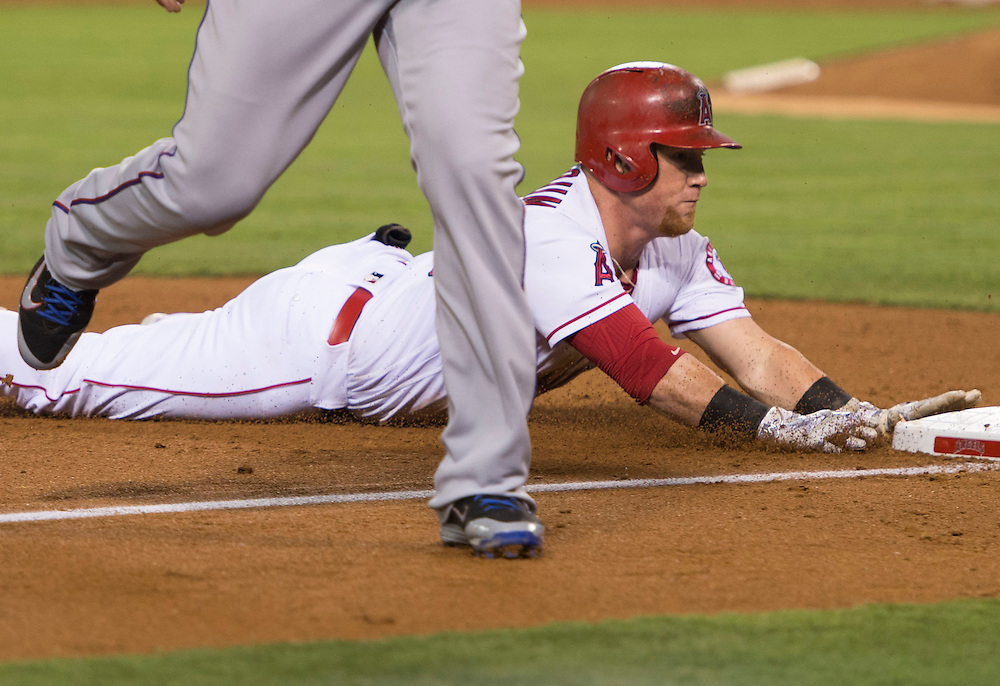 The Angels' Kole Calhoun slides into third base past the Rangers' Adrian Beltre after his triple to lead off the fifth inning against the Texas Rangers at Angel Stadium on Tuesday.<br /> <br /> ///ADDITIONAL INFO:   <br /> <br /> angels.0720.kjs  ---  Photo by KEVIN SULLIVAN / Orange County Register  -- 7/19/16<br /> <br /> The Los Angeles Angels take on the Texas Rangers at Angel Stadium.