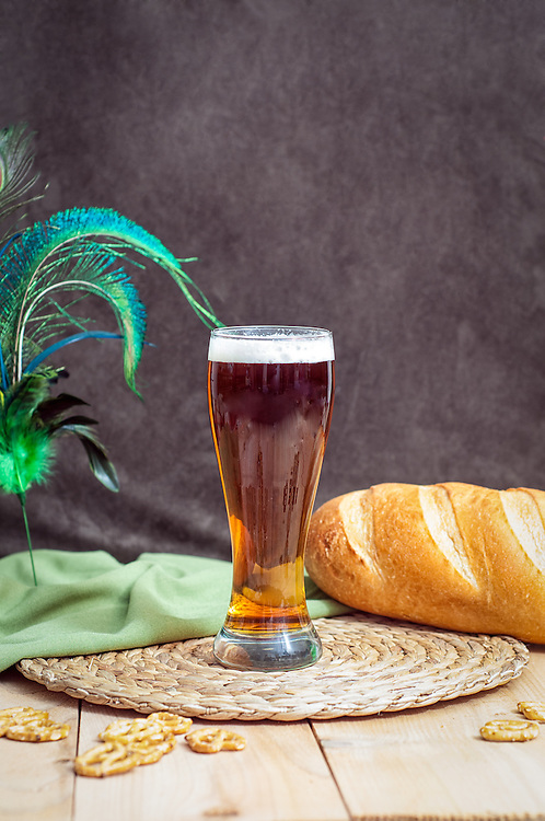 A glass of dark ale with bread and pretzels.
