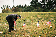 10 SEPTEMBER 2020 - DES MOINES, IOWA: RON VANDERKAMP, a volunteer puts out American flags on the shore of Gray's Lake. About 25 volunteers braved cold and rainy weather Thursday to line the west end of Gray's Lake in Des Moines with American flags. The display of flags was a part of an annual event called the 9/11 Tribute Trail. About 3,000 flags were set out in memorial of the 3,000 people killed in the 9/11 terrorist attacks.     PHOTO BY JACK KURTZ