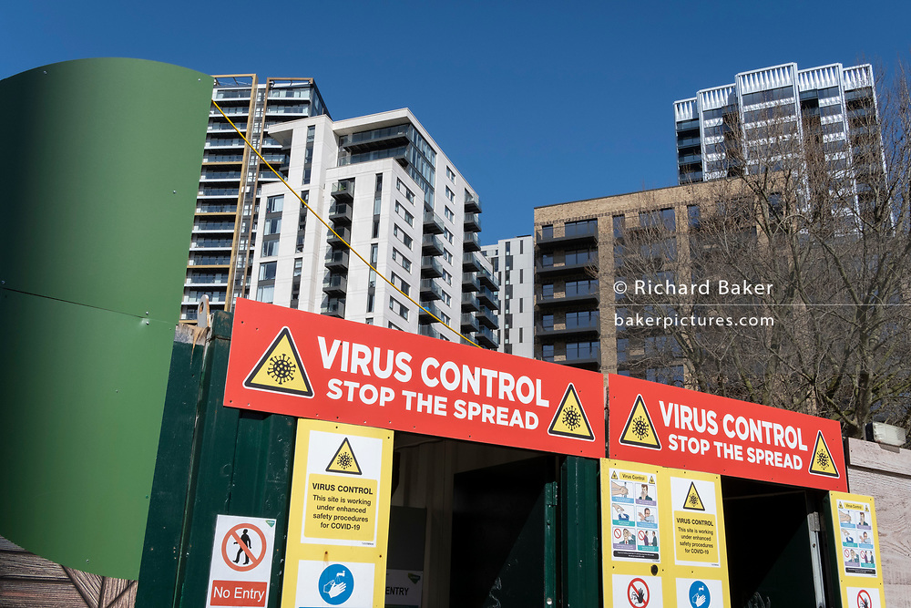 New housing at Elephant Park in the south London borough of Southwark, rises over a works site entrance with Coronavirus pandemic virus control warnings during the third lockdown of the Coronavirus pandemic, on 29th March 2021, in London, England.