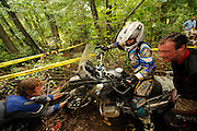 Brad ? pulls on front wheel of R1200GS at BMW GS Challenge event while Briene Thompson rides bike and Bill Dragoo strains to lift rear wheel.
