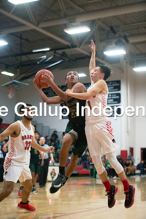 Newcomb Skyhawk Deondre Begay (22) drives to the basket as Grants Pirate Eddie Baca (3) defends in the Eddie Peña Classic Basketball Tournament Friday, Dec. 20  in Grants.