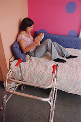 Teenage girl with physical disability sitting on bed reading book,