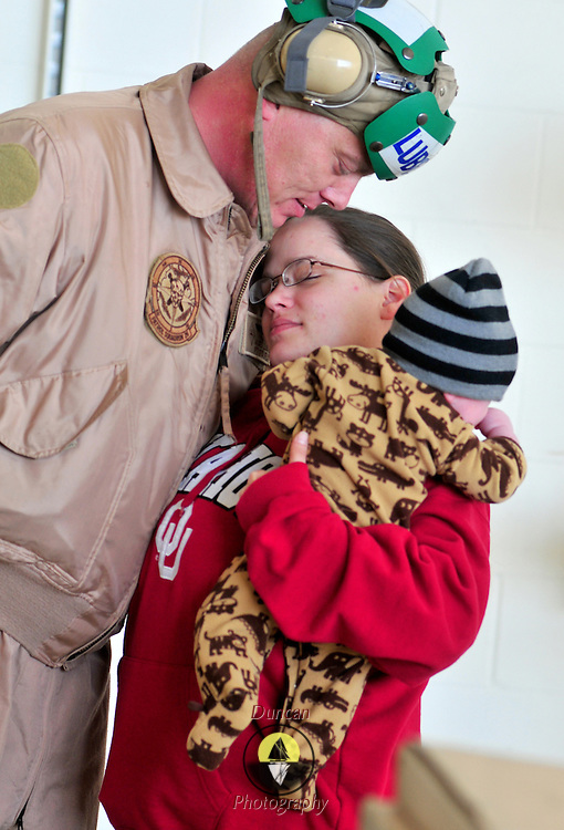 11/22/09 -- BRUNSWICK, Maine. Rachael Maurer hugs her husband, Petty Officer First Class James Lubitz while holding their son, Logan. Petty Officer Lubitz, of the Navy's P-3 Patrol squadron VP-26,  deployed on Sunday to Africa with a crew from Naval Air Station Brunswick. The squadron will deploy it's last two planes on Sunday after Thanksgiving. The squadron will deploy it's last two planes on Sunday, after Thanksgiving. Following the deployment, VP-26 will return to Jacksonville, Fla., because NAS Brunswick is slated to close in 2011.  VP-26 is the last squadron to leave NAS Brunswick. Photo by Roger S. Duncan