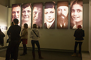 Visitors standing beneath panels with the faces of Jewish victims of the Holocaust, read the stories and history of Nazi anti-Semitism, in central Berlin, Germany.