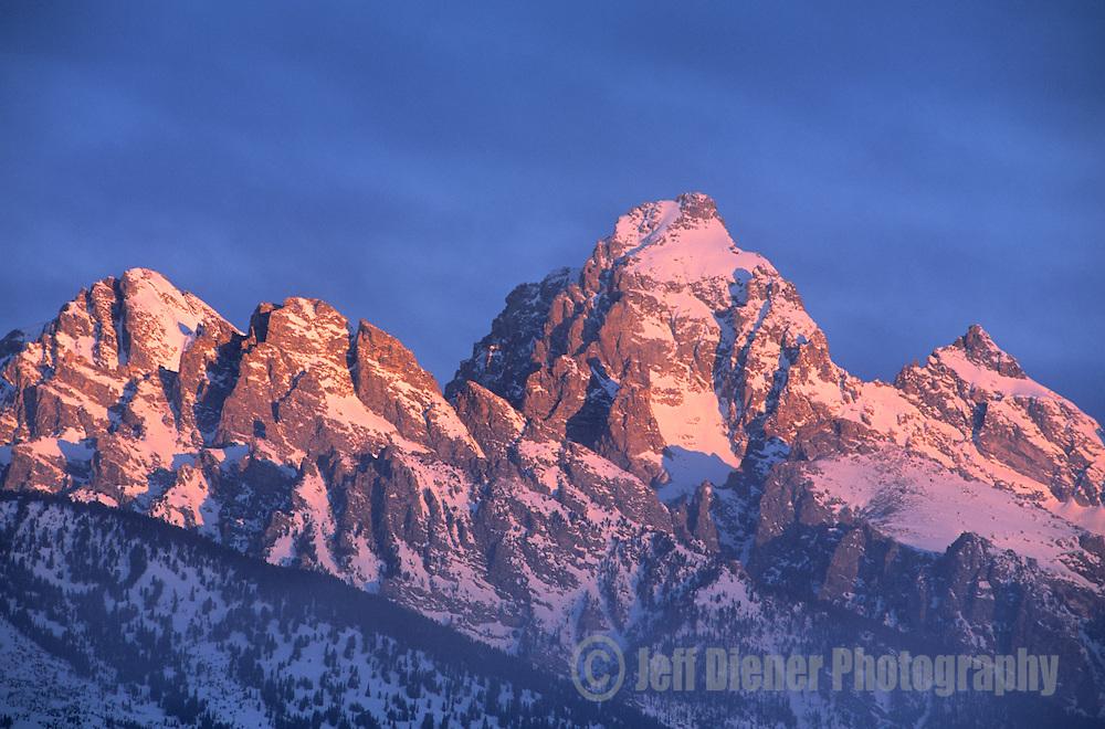 Sunrise illuminates the high peaks of the Tetons in Grand Teton National Park, Wyoming.
