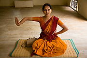 "Ganga Thampi, teaches young  trainee dancers  movement, rhythm and expression, known as ""nritya"" and seen here a lesson in ""abhinaya"", or stylized expressions at the traditional and highly prestigious Kalakshetra school for the arts, Chennai. The school was founded in 1936 and due to its exacting and demanding schedule is considered India's formost classical dance academy of this ancient cultural art heritage that is informally known as ""temple dancing"" and that dates back to the Natya Shastra, the 2000 year old text that lays down the principles of Indian dramatic theory and performance. Tamil Nadu, India."