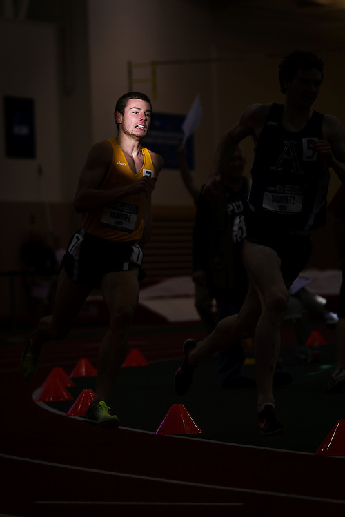 Greg Whittle of Calvin College rounds the corner into the sun during the Men's 1 Mile run on Friday of the NCAA Division III Indoor Track and Field National Championships at Grinnell College.