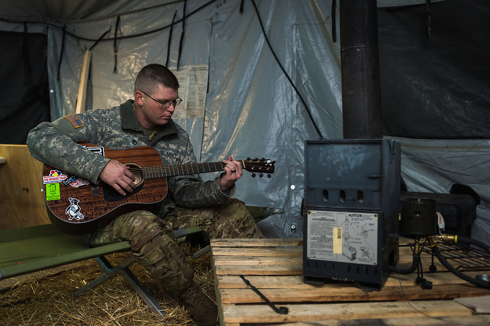 Staff Sgt. Thomas Gorman spends a few quiet moments honing his skills with the guitar on a cold evening. Personal pursuits such as playing instruments, photography, or illustration are common amongst soldiers in the field even if such practices may not be the most pleasant to the ears of their compatriots.