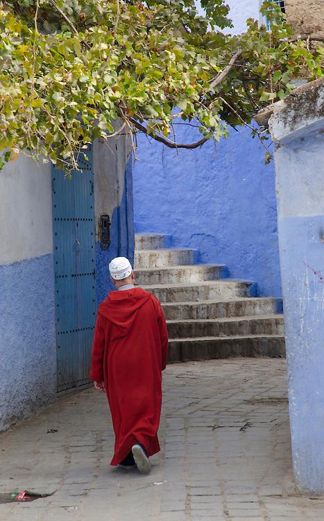 A man in jellaba walks through medina, Chefchaouen, Morocco