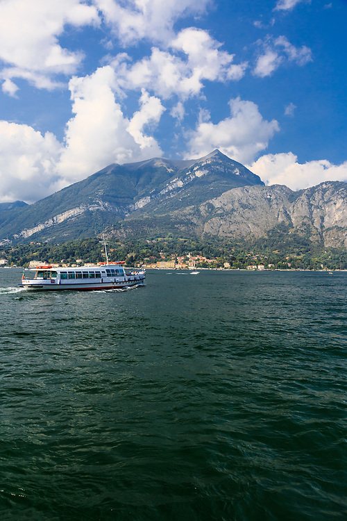 A ferry crosses Lago di Como in Italy.<br /> Boat trips and tours are the easiest way to move around the lake and experience its atmosphere with a more relaxed way.  <br /> The local public navigation service (Navigazione Laghi) provides several routes that connect all of the most popular towns along Lake Como's shores at a convenient price.