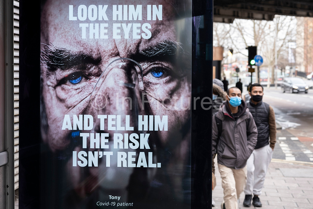 Men wearing face masks approach a bus stop advertising screen showing slogans and the faces of coronavirus patients which are part of the latest NHS, HM Government campaign to encourage people in Britain to take the virus seriously as the national coronavirus lockdown three continues on 28th January 2021 in London, United Kingdom. Following the surge in cases over the Winter including a new UK variant of Covid-19, this nationwide lockdown advises all citizens to follow the message to stay at home, protect the NHS and save lives.