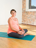 A pregnant woman (20-30 years old) sits on a yoga mat, smiling.