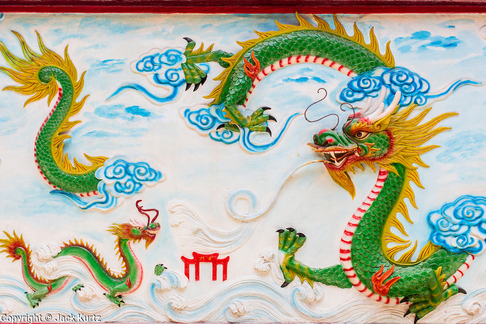 """12 APRIL 2012 - HO CHI MINH CITY, VIETNAM:   A relief of a Chinese dragon in Chùa Quan Âm (Avalokiteshvara Pagoda), a Chinese style Buddhist pagoda in Cho Lon. Founded in the 19th century, it is dedicated to the bodhisattva Quan Âm. The pagoda is very popular among both Vietnamese and Chinese Buddhists. Cholon is the Chinese-influenced section of Ho Chi Minh City (former Saigon). It is the largest """"Chinatown"""" in Vietnam. Cholon consists of the western half of District 5 as well as several adjoining neighborhoods in District 6. The Vietnamese name Cholon literally means """"big"""" (lon) """"market"""" (cho). Incorporated in 1879 as a city 11km from central Saigon. By the 1930s, it had expanded to the city limit of Saigon. On April 27, 1931, French colonial authorities merged the two cities to form Saigon-Cholon. In 1956, """"Cholon"""" was dropped from the name and the city became known as Saigon. During the Vietnam War (called the American War by the Vietnamese), soldiers and deserters from the United States Army maintained a thriving black market in Cholon, trading in various American and especially U.S Army-issue items.        PHOTO BY JACK KURTZ"""