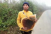 A Tai Lue ethnic minority man walks along the road carrying a large honeycomb, Oudomxay province, Lao PDR. For many families food caught or collected from the wild, especially edible plants and small animals still make up fifty per cent of their diet.