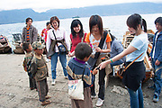 Domestic Chinese tourists buying items from very young hawkers at Lugu Lake, Yunnan, China. Lugu Lake is located in the North West Yunnan plateau in the centre of Ninglang Yi Autonomous County in the Peoples Republic of China.