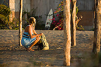 Young woman looking through pack after surfing. Mexico.