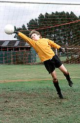 Young boy saving goal during football match,