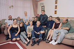 Father with Alzheimer's disease sitting at home with three generations of his family,