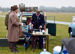 © Licensed to London News Pictures. 13/09/2013. Chichester, UK Men enjoy a bacon sandwich cooked from the back of a car. People enjoy the atmosphere at the 2013 Goodwood Revival. The event recreates the glorious days of motor racing and participants are encouraged to dress in period dress. The revival is the only event of its kind to be staged entirely in the nostalgic time capsule of the 1940s, 50s and 60s Photo credit : Stephen Simpson/LNP.