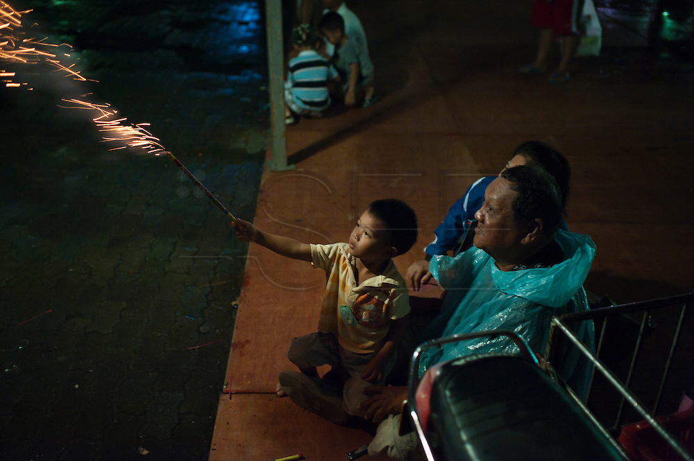 A boy plays with fireworks during the Vegetarian Festival in Thailand. Every year during the ninth lunar month of the Chinese calendar, the Phuket Vegetarian Festival kicks off. The religious festival in Phuket, Thailand, lasts for 10 days, during which sacred rituals take place in the many Chinese shrines and temples. Walking on fire and climbing ladders with bladed rungs barefoot are two of several rituals believed to bring good fortune. The main purpose of the festival, however, is spiritual cleansing and merit-making. The origins of the festival date back to 1825, when a traveling Chinese opera company came to Phuket to perform for the miners there. An epidemic broke out and as the members of the company fell sick, they adhered to a vegetarian diet to honor two of the Emperor Gods, Kiew Ong Tai The and Yok Ong Sone Teh. When they became well again shortly thereafter, the people of Phuket followed the companyÕs example - and have celebrated the festival ever since to bring good luck to their communities.