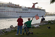 Two older women watch a large cruise ship leaving Miami Port and one holding the American flag waves goodbye to friends on board the boat