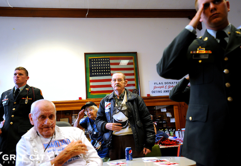 Spc. Nate Clements, l-r, Edwin McMarland, John Tyler, and Spc. Gregory Baker show their respect during the playing of the National Anthem at a Veteran's Day ceremony at the Washington Soldier's Home in Orting Nov. 11. Clements and Baker and other Soldiers from 1-94 FA spent time visiting the home's residents during the event.