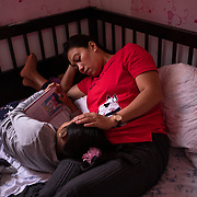 Vanessa Mae Rodel, 42, and her seven-year-old daughter Keana Nihinsa, read a child's bible book at their home in Hong Kong, on March 21, 2019. / Photo: Maria de la Guardia
