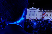 A man with a glowing earphone cable watches a protest in front of the White House. Blacklight photography.