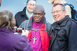 © Licensed to London News Pictures. 02/12/2015. Robin Hood's Bay UK. Dr John Sentamu, The Archbishop of York posses for a photograph with a member of the public as he begins a six month pilgrimage around Yorkshire. He will walk between each of the 21 deaneries of the Diocese of York & is inviting members of the public to join him. He will travel through the Archdeaconry of the East Riding and finish at York Minster on 22 May next year. Photo credit:  Andrew McCaren/LNP