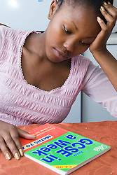 Girl sitting at kitchen table studying for school exams,