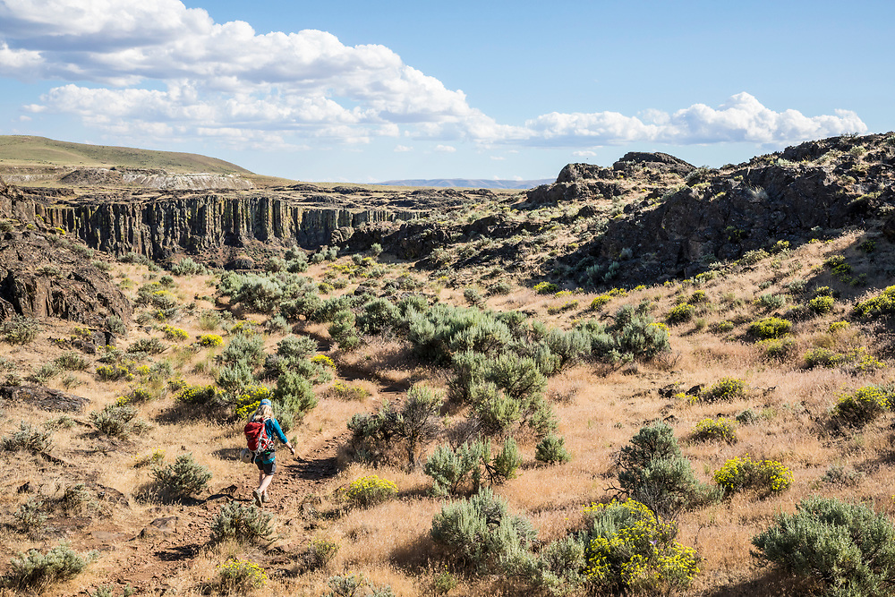A woman hiking on a trail wearing a rock climbing harness and carrying a backpack near Frenchmans Coulee headed toward Echo Basin in Eastern Washington, USA