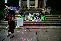 July 19, 2017 - Minneapolis, Minnesota, U.S. - A woman views the memorial on the steps of the Lake Harriet Spiritual Community church in south Minneapolis on Wednesday, as rain began to fall. An Australian woman was shot and killed by a Minneapolis police officer on Saturday after she called 911 to report a possible assault near her home. (Credit Image: © Aaron Lavinsky/TNS via ZUMA Wire)