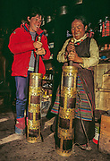 Trekker and Sherpani use butter-tea churn, Kunde village, Khumbu Himal, Nepal