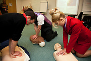 Intense medical session for trainees, here practicing CPR on dummies. Virgin Atlantic air stewardess and steward training at The Base training facility in Crawley. Potential hostesses are put through a gruelling 6 week training program, during which they are tested to their limits. With exams every day requiring an 88% score to pass. The Base is a modern environment for a state of the art airline training situated next to Virgin Atlantic's HQ.