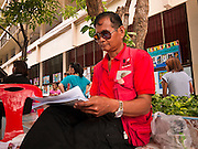 "03 JULY 2011 - BANGKOK, THAILAND:   A Pheu Thai election monitor watches for voting irregularities in Bangkok, Thailand, Sunday July 3. Pheu Thai is the party of the Thai ""Red Shirts"" who held months long protests in Bangkok in 2010. More than 47,000,000 Thais were registered to vote in Sunday's election, which had turned into a referendum on the current government, led, by the Thai Democrats and the oppositionPheu Thai party. Pheu Thai is the latest political incarnation of ousted Thai Prime Minister Thaksin Shinawatra. PT is led by his youngest sister, Yingluck Shinawatra, who is the party's candidate for Prime Minister. Exit polling by three Thai polling firms showed Pheu Thai winning a landslide election.   PHOTO BY JACK KURTZ"